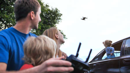 A friendly family launches a drone and controls it through the control panel.