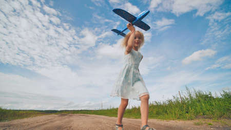 A little girl runs and launches a paralon toy airplane.