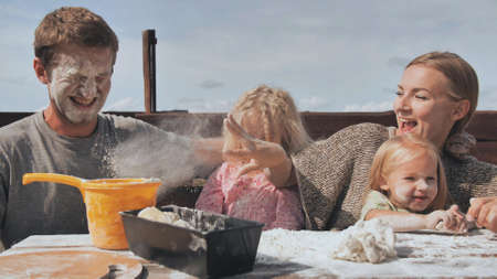 The young family knead the dough for bread and throw flour at each other.