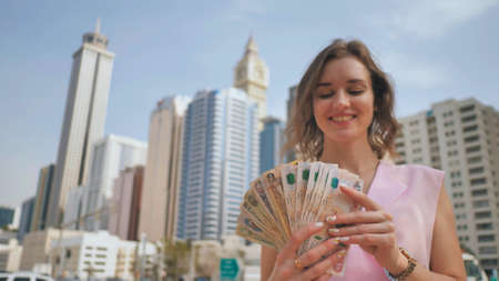 The girl holds in her hands the money of the United Arab Emirates on the background of the city center of Dubai.