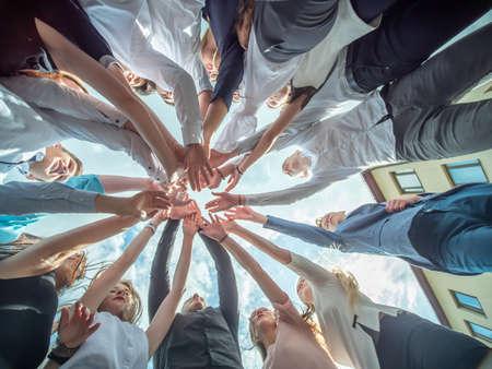 友好的な友人は、共同ビジネスの兆候として手を組みます。チームとコミュニティのコンセプト 写真素材