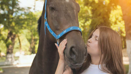 Young seventeen year old girl kisses her beloved horse.