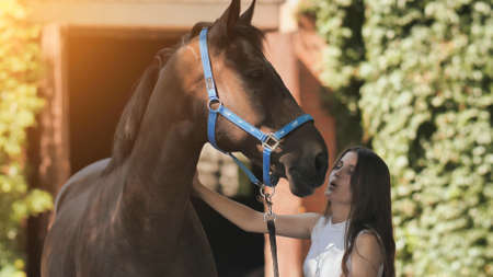 A young girl kisses her beloved horse.