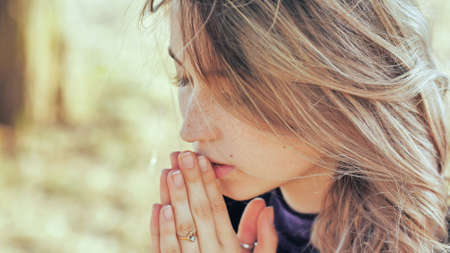 A young blonde 18 year old girl prays with folded hands.