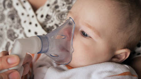 Funny one year old baby breathes with an inhaler Standard-Bild
