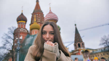 Happy smiling young woman portrait in Red Square, Moscow. A woman in the city warms her hands. Banco de Imagens