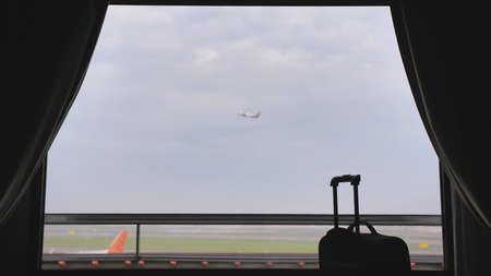The window of the hotel near the airport and the plane taking off in the background of a suitcase or luggage.