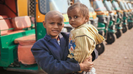 Agra, India - December 12, 2018: A little beggar boy holds a baby in his arms against the background of a rickshaw.