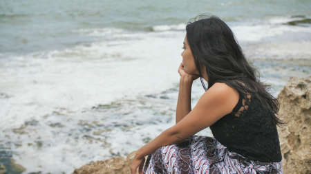 Indonesian girl sad on the rocky shore of the island of Bali.
