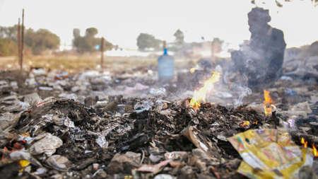 Burning trash and poor Indian old man. Foto de archivo
