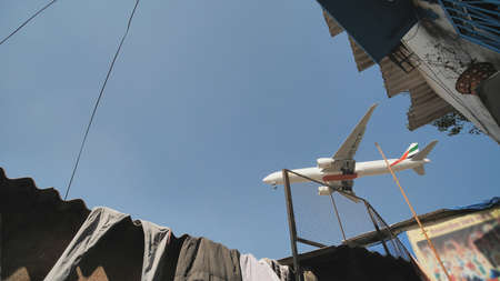 The plane lands low over the slums of the city of Mumbai.