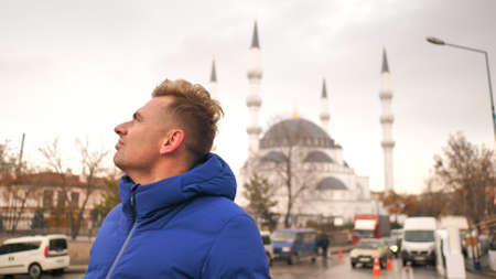 Tourist in the winter against the background of a mosque in Ankara.