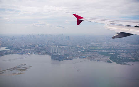 The plane flies against the background of the city of Jakarta. Indonesia.