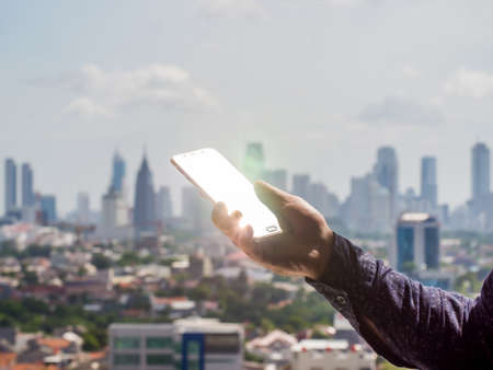 A man holds a phone in his hand that shines a ray of sunshine against the background of the city of Jakarta. Indonesia.