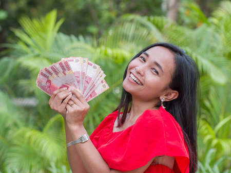 Indonesian money in the hands of an asian girl.