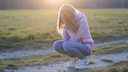 Girl 12 years old crying squatting in the sunset.
