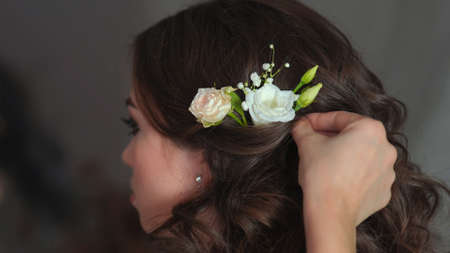 The stylist adorns the girl's hair with delicate flowers Stock Photo