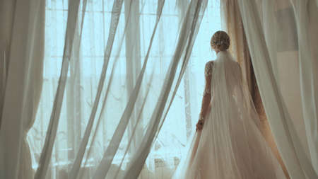 Happy bride is spinning at the window