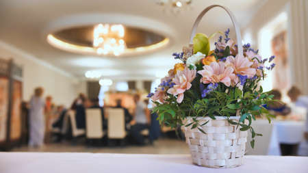 Wedding celebration background concept. A bouquet of flowers on the background of the banquet guests who are eating Zdjęcie Seryjne