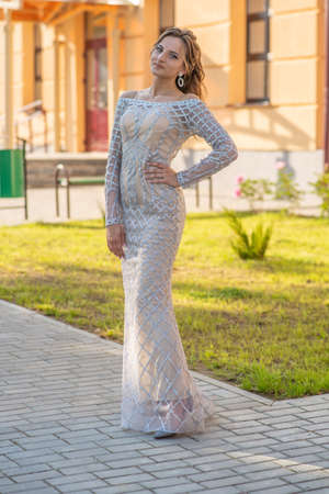 Russian graduates posing in a beautiful dress against the backdrop of their school.