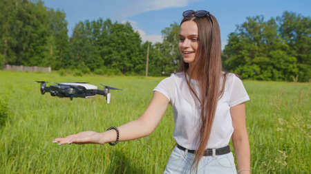 The girl launches a drone from her hand in the park.