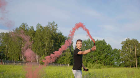 The guy sprays colored red smoke in the meadow on a summer day.
