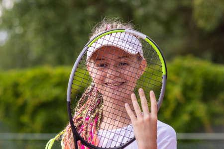 An aspiring smiling girl tennis player looks through a tennis racket.