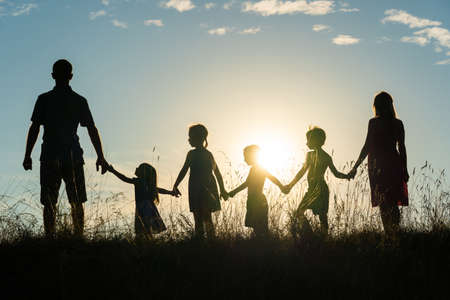 Silhouette of a happy large family at sunset. 版權商用圖片