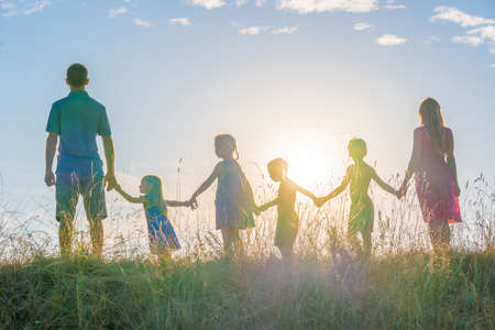 A large family is standing holding hands against the background of the sunset.