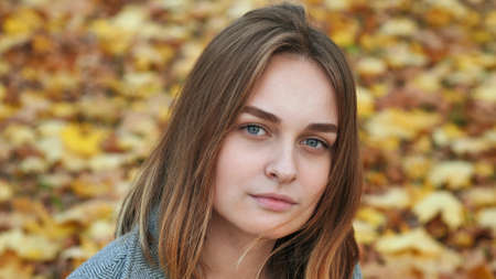 Portrait of a young and beautiful girl against a background of yellow leaves. Face close up.