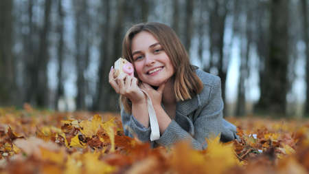 A young beautiful girl takes pictures in an autumn park using a toy camera.
