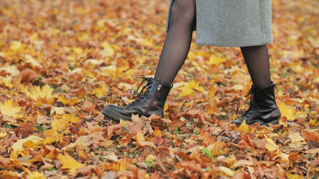 A girl in warm boots walks over the fallen leaves.