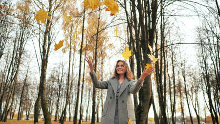 A young girl throws up leaves in an autumn park.