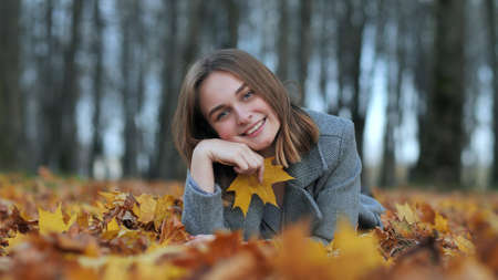 Beautiful happy young girl with a smile holds an autumn yellow leaf near the face. 写真素材