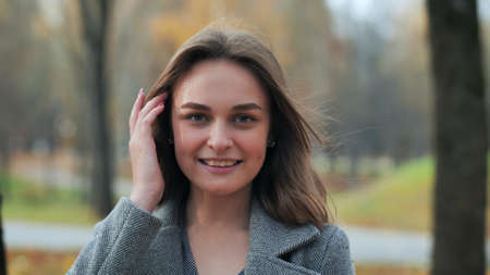 Portrait of a smiling young girl in an autumn park.