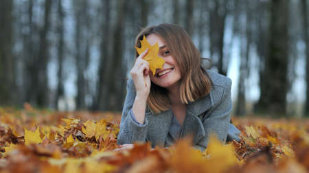 A young girl in an autumn park lies on the leaves and smiles with a leaf in her hand. 写真素材