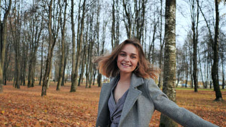 A beautiful and happy girl is walking in the autumn park.