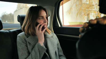 The girl in the car is talking on the phone.