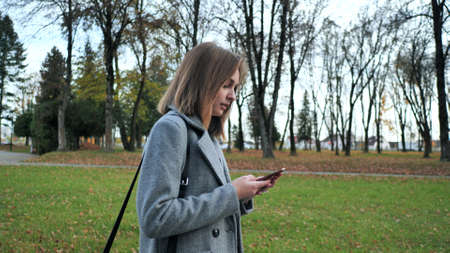 A young girl walks through the autumn park and dials a number on the phone.
