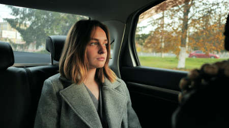 A sad young girl drives in a car salon in the fall.