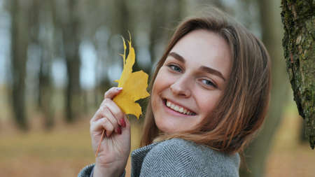 Beautiful happy young girl with a smile holds an autumn yellow leaf near the face
