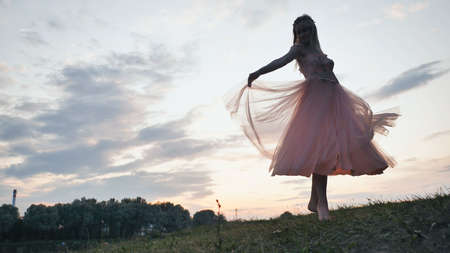 The girl in the dress swirls magically at sunset.