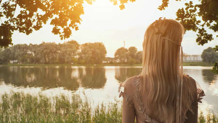 Beautiful young blond woman outdoors portrait near the lake.