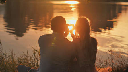 Silhouette of a young couple making a heart shape from their hands.