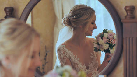 The bride at the mirror with a bouquet of flowers. 写真素材