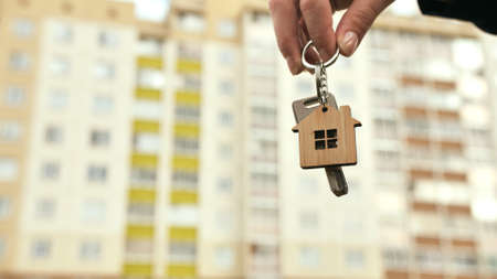 The concept of buying a new apartment. The girl holds the keys to a new apartment.