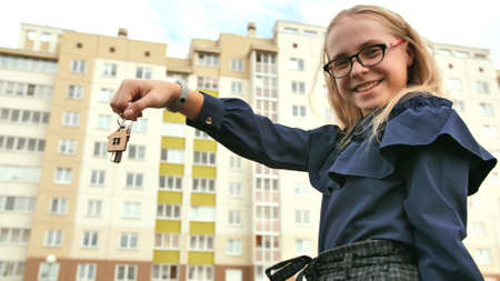 A young schoolgirl holds the keys to a new apartment.