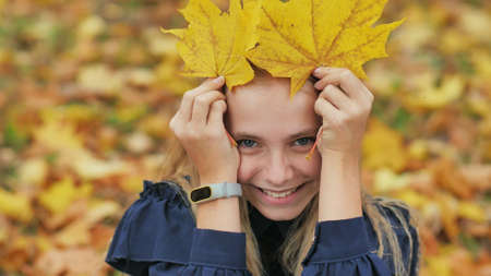 A young girl of 13 years old with autumn leaves poses in front of a photo camera.