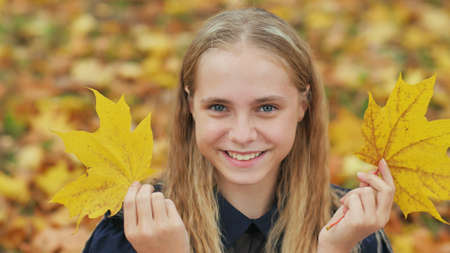 A young girl of 13 years old with autumn leaves poses in front of a video camera. 写真素材