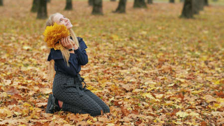 Teenager girl collects autumn leaves in the park and posing.